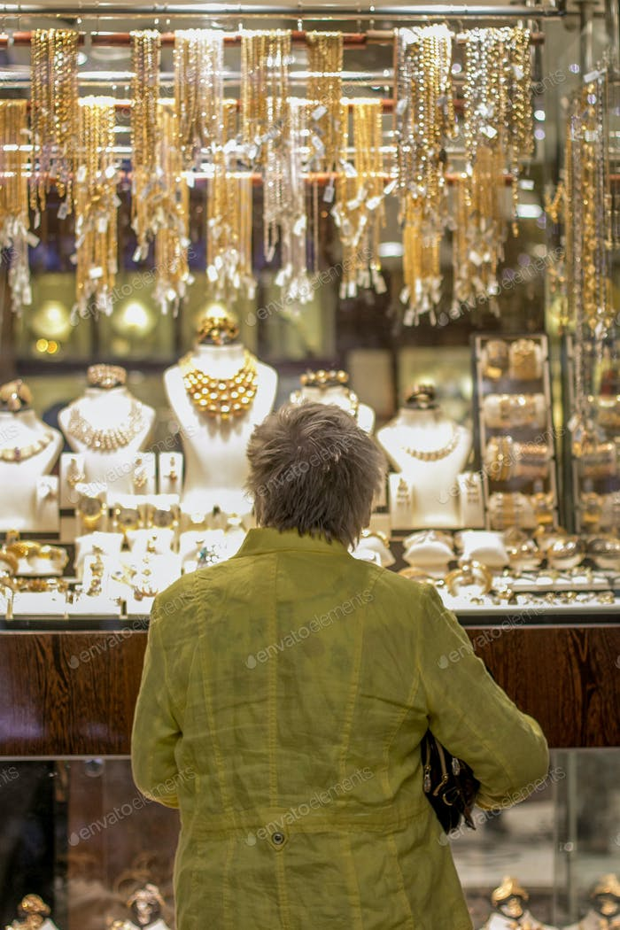 Woman looking at gold display in Dubai Gold Souq.