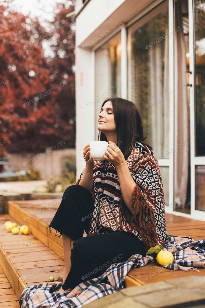 Young woman sitting on wooden porch of a cozy country house and drinking hot tea.