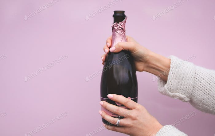 A woman's hands holding a bottle of pink champagne in front of a pink wall