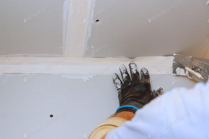 Hausverbesserungen. Putting Gips an der Wand mit Spachtel Hand halten Putzwerkzeug