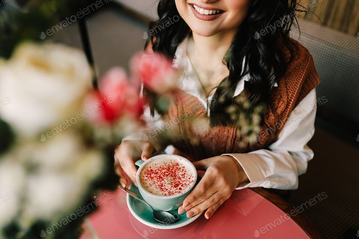 Beautiful bright emotional curly brunette young woman with makeup in a cafe; cup of coffee; mobile;