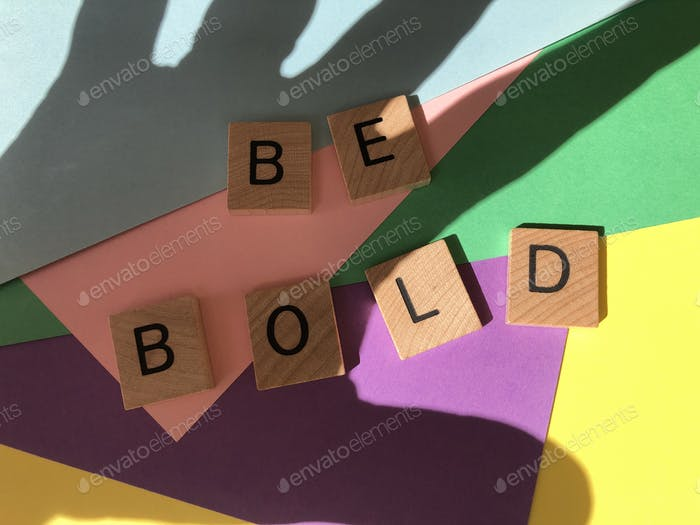 Be Bold in wooden alphabet letters on a colourful multicoloured background with the shadow of a