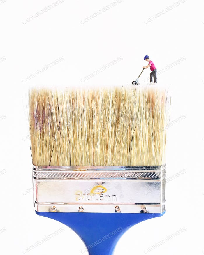 Tiny man mowing a large natural hair bristle paintbrush against a white background.