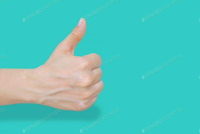 Cerca de la mano femenina mostrando gesto de pulgar hacia arriba sobre fondo azul pastel con trazado de recorte.