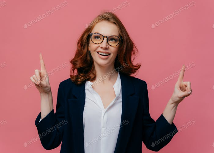 Joyful redhaired woman looks above, points fore fingers upwards, has satisfied facial expression