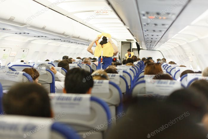 safety technique on the plane, stewardess shows how to put on a vest