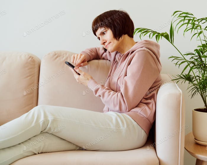 Portrait of mature woman looking on mobile phone with surprise and alarm, confusion and frown