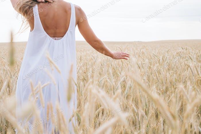 Frau zu Fuß durch Feld Berühren Gräser