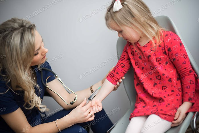 Brave little girl receiving injection in doctor