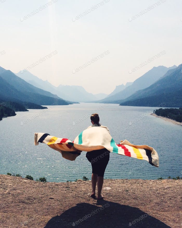 That mountain view, though. Girl with blanket by mountain lake.