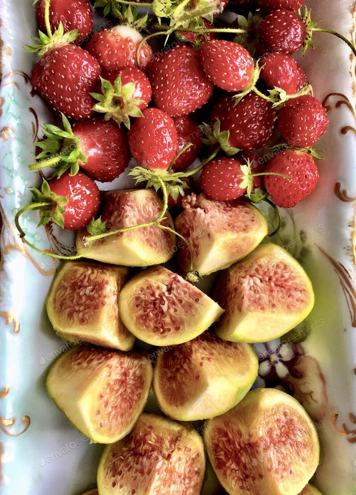 Fresh strawberries and figs displayed on an antique dish.