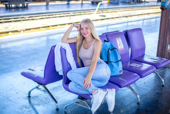 Portrait of young woman on traveling waiting train at the station.