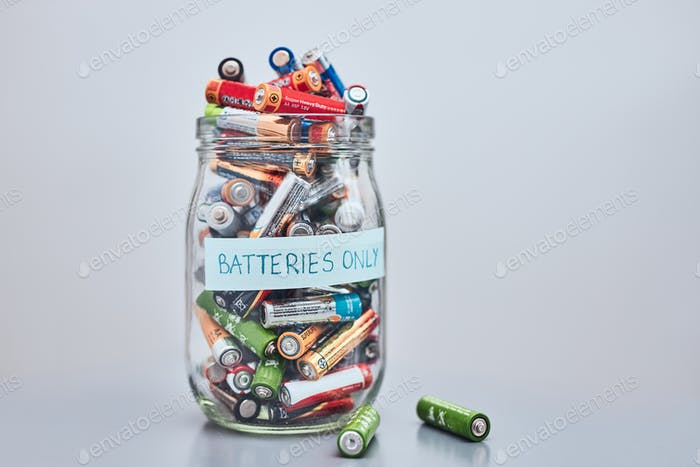 Jar filled with discharged used batteries. Waste disposal and recycling. Separating the waste