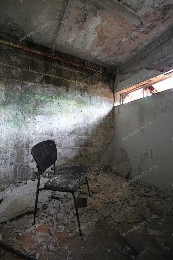 A derelict, deserted, abandoned room with a single chair sat on rubble like a prison or jail.