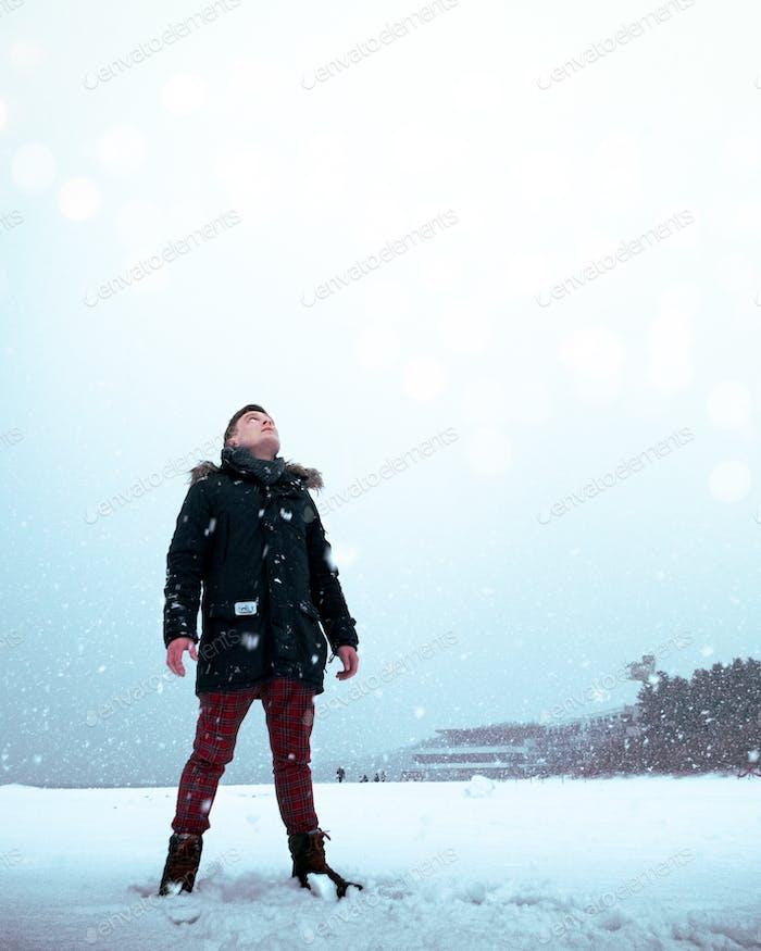 Vista de ángulo bajo de un joven mirando en el cielo nevando.