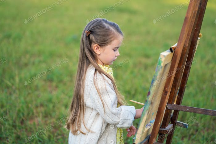 Girl paints a landscape on an easel with paints in nature