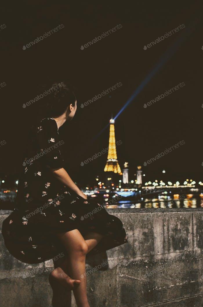 Schönes Mädchen beobachten die Lichter auf dem Eiffelturm an der Spitze der Stunde.