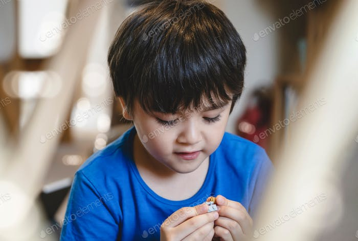A boy playing plastic blocks,Child with smiling face sitting alone playing with toys in living room