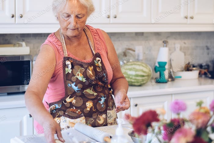 A woman is baking in a bright white modern kitchen. Seniors lifestyle