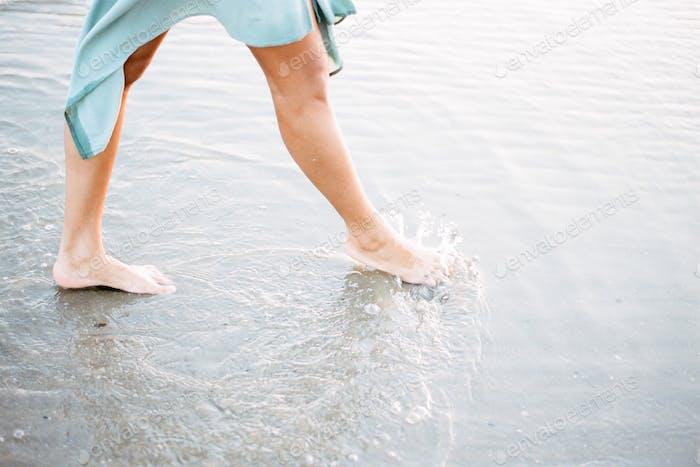 Feet of a Young woman on the beach wearing a beautiful blue dress. Walking in the ocean. Fine art st