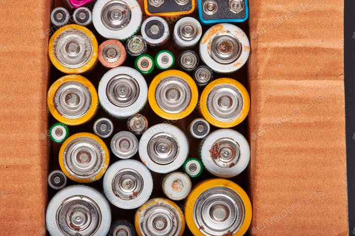 Discharged batteries in cardboard box. Collecting used batteries to recycle. Waste disposal
