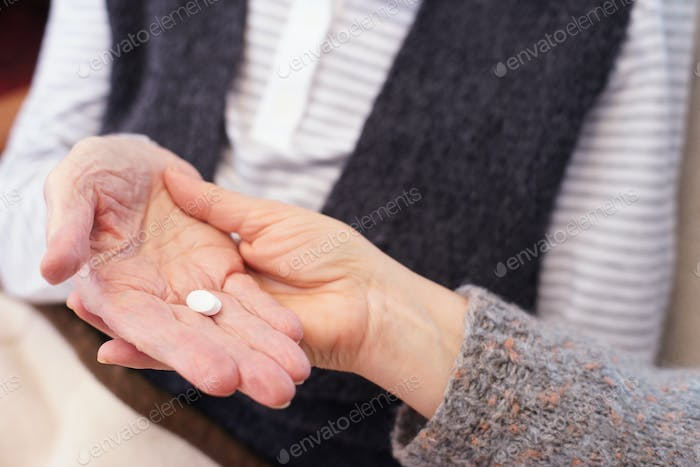 Senior hand with caregiver and pill