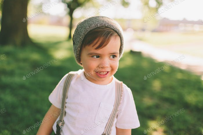 A portrait of a happy little boy wearing suspenders and a hat.