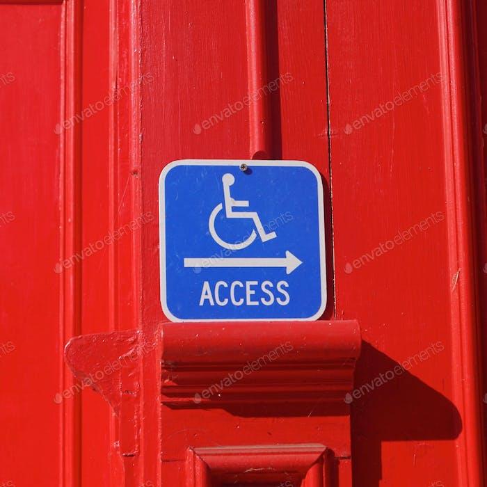Die Welt zu einem besseren Ort machen. Rollstuhl-Schild auf rotem Hintergrund.