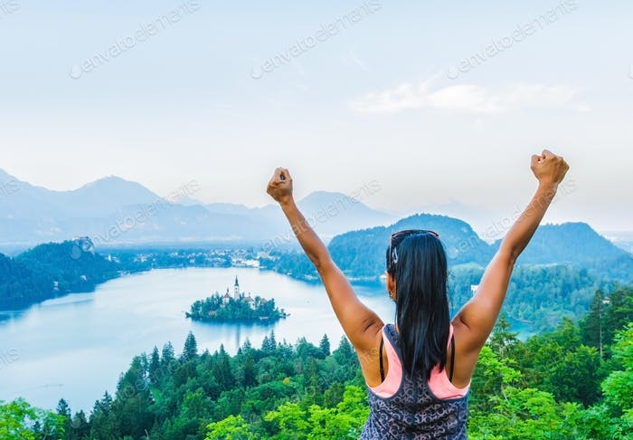 Woman finishing hiking to top of mountain at view point with breathtaking scene of lake Bled in Slov