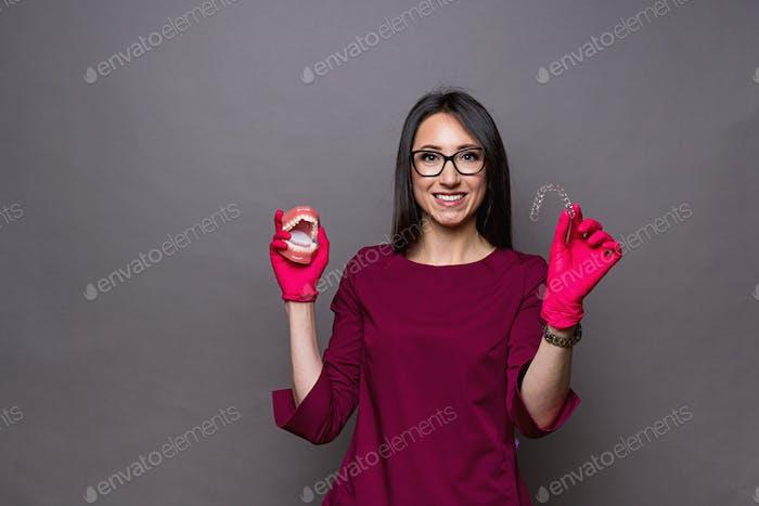 Eine positive brünette Zahnärztin mit schneeweißem Lächeln in einer kastanienbraunen Uniform mit Alignern