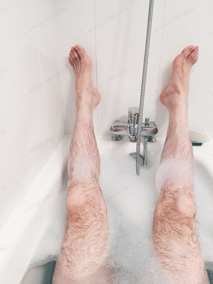Exhausted young man in the bath, legs up, white bathroom