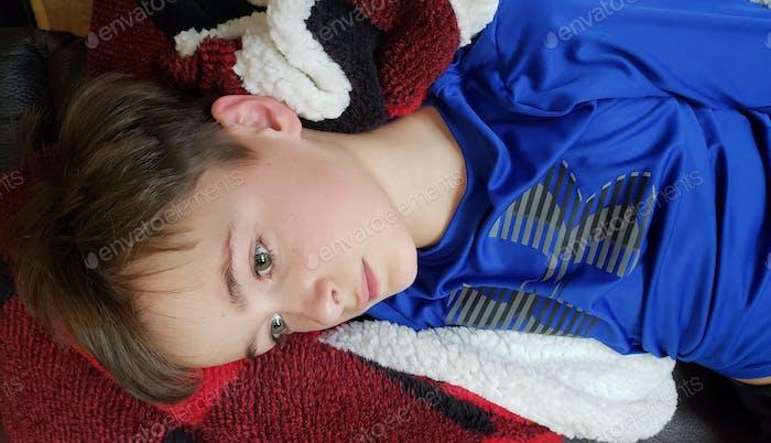 Kleiner Junge, der an einem regnerischen Tag sehr gelangweilt auf der Couch liegt und sich fragt, wie er seine Freunde schleichen kann