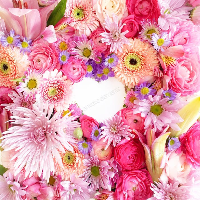 Heart shape formed in the negative space of arranged brightly colored blooming flowers.