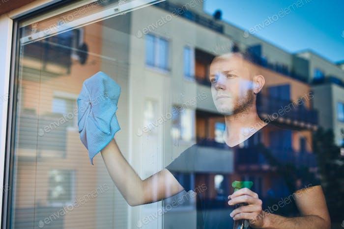 Mann Reinigungsfenster mit Lappen und Reinigungsspray zu Hause. Themen Hausarbeit und Hauswirtschaft.