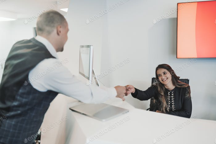 A businessman and woman receptionist