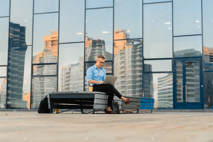 Young Professional Businessman working online on laptop in city. Typing check email has video chat