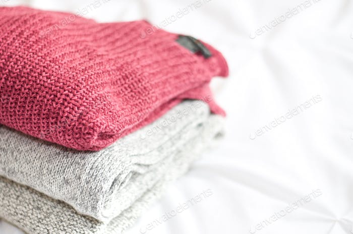 Comfy and cozy knit sweaters stacked on a bed.