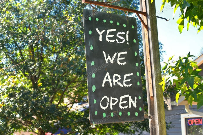 OPEN!! Chalkboard sign hanging outside says Yes We Are Open!! With neon OPEN sign background window