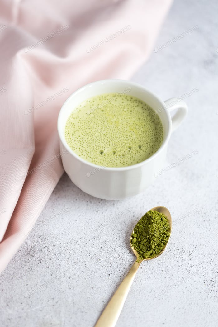 Matcha latte in white mug with gold spoon with pile of matcha powder.