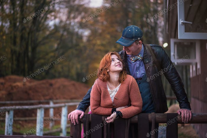 Guy and a girl are standing next to each other in the countryside near the stables
