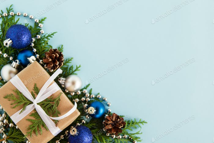Christmas flat lay composition of fir branches with gift box and decorations at the left corner with