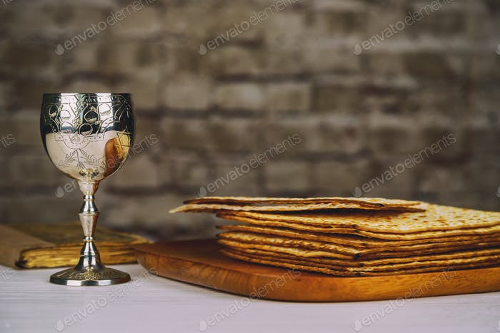 Red kosher wine with a white plate of matzah or matza and a Passover Haggadah on a vintage wood