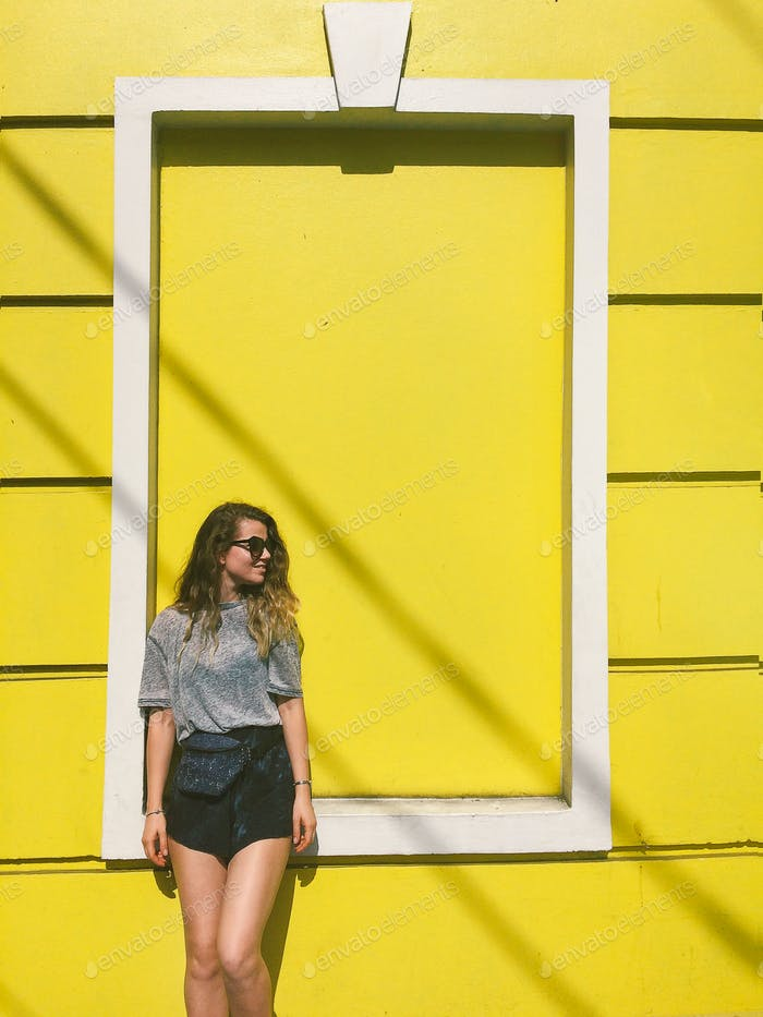 Young beautiful girl standing next to the yellow wall
