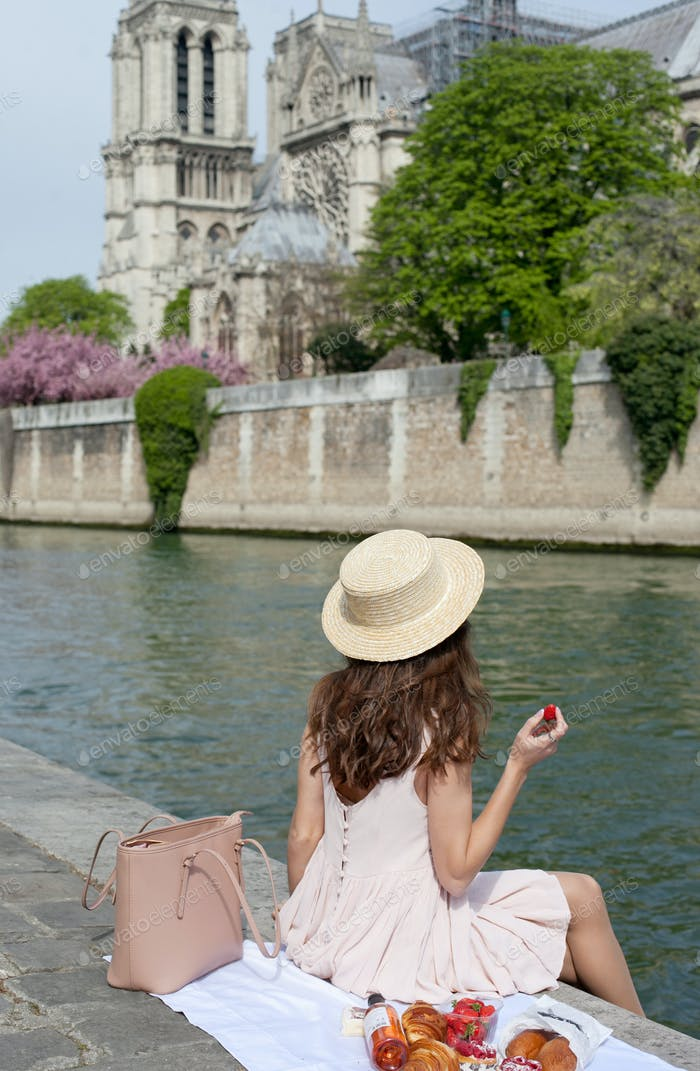 A young woman wearing a straw hat having a picnic by the river in Paris, with the view of Notre Dame