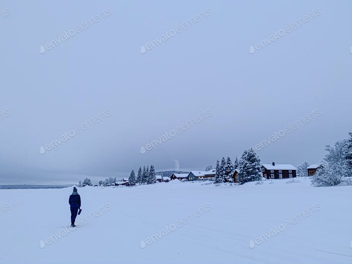 A girls standing on a frozen river overlooking small Swedish village in the evening