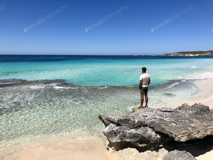 Young man looking the pristine sea from a rock on the beach