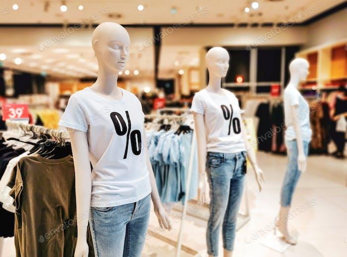 Verkauf Schild auf Mannequin im Bekleidungsgeschäft.
