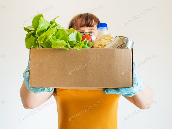 Delivery girl wearing face mask with food staples and fresh produce in a box. Safe delivery