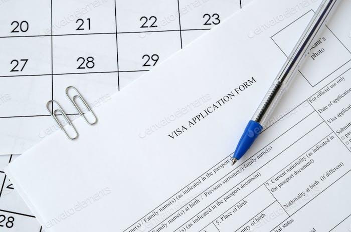 Formulario típico de solicitud de visado y bolígrafo azul en papel página de calendario de cerca