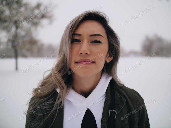 Young woman looking directly at camera smirk happy peaceful outside in snow during winter smiling